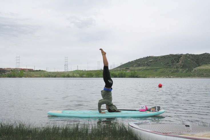 Lindsay Gonzalez does a headstand on her paddleboard on May 15 during the Golden Games at Soda Lakes. Gonzalez, of Golden, is a stand-up paddleboard yoga instructor and athlete.