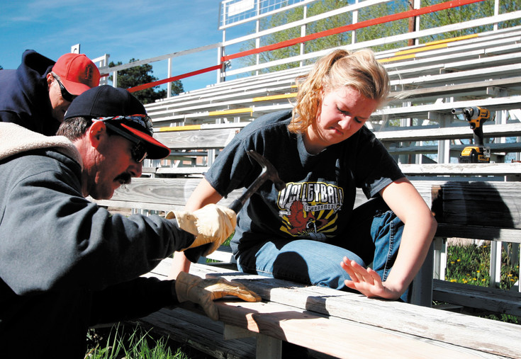 Joel Birchem and 2016 Stampede Queen Kelly Sweigart attach new seating to the west grandstand at the Elizabeth Stampede Grounds on May 16.