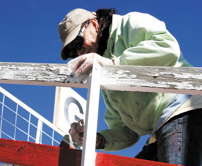 Linda Almquist applies a new coat of paint to the grandstand railing at the Elizabeth Stampede Grounds on May 16.