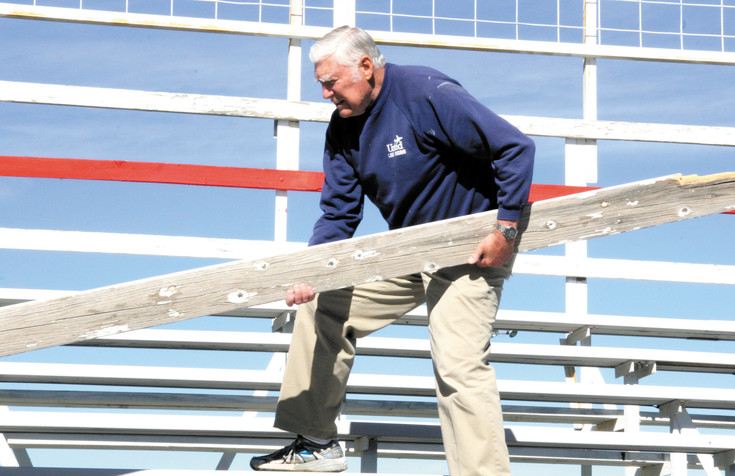 Don Johnson removes a splintered grandstand plank.