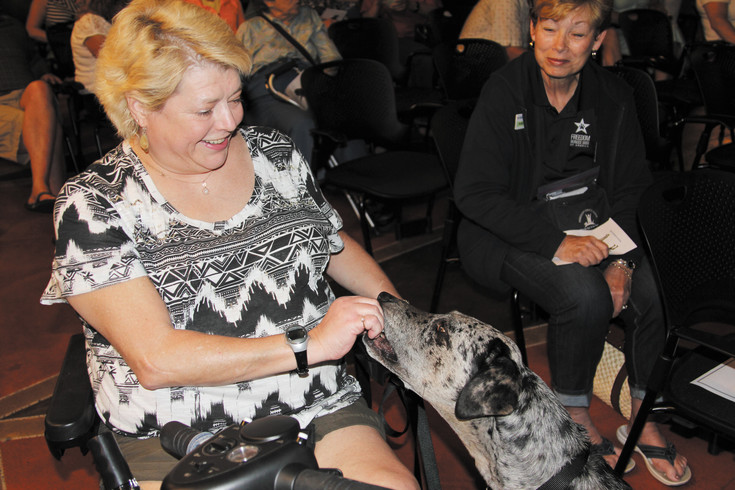 Chris Mangold gets the full attention of Tula as they wait their turn to receive their diplomas during the June 6 Freedom Service Dog graduation ceremonies. Tula has been trained to provide specific services to Mangold, who is legally blind and in a wheelchair.