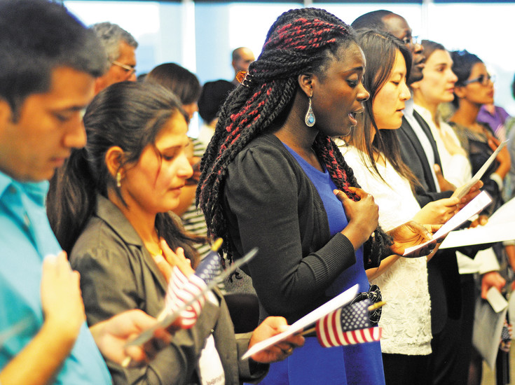Newly naturalized citizens sing the national anthem for the first time as an American citizen at a naturalization ceremony held at the U.S. Citizen and Immigration Services building in Centennial on June 8. In middle, wearing blue is Bridgette Yeboah-Spaun, who's originally from Ghana. Yeboah-Spaun said now that she's a nurse in the U.S., her plans are to build a clinic back in her home village.