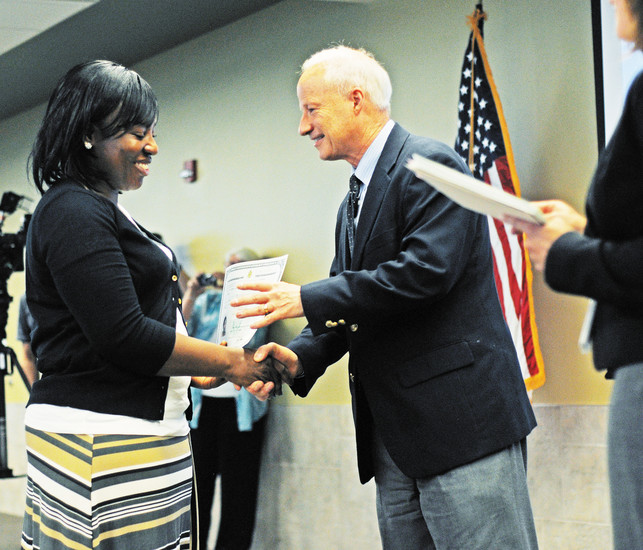 Congressman Mike Coffman shakes the hand of newly naturalized American citizen Barbara Lawrence at a naturalization ceremony June 8 at the U.S. Citizen and Immigration Services building in Centennial.