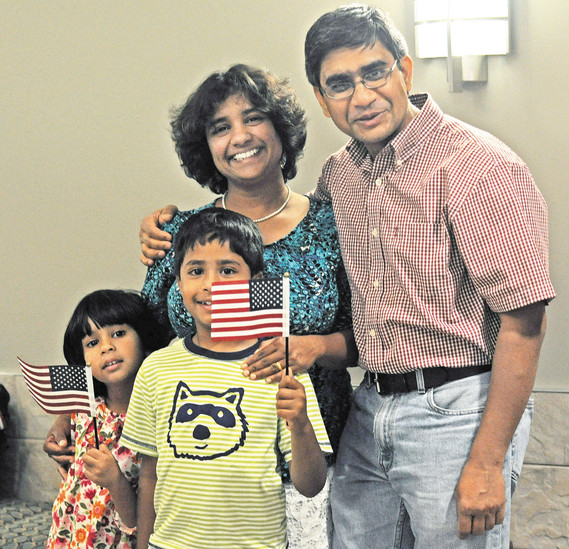 Newly naturalized American citizen, Madhu Kamar, back left, smiles as she poses for a photo with her husband Sunil and children Anika, left, and Ayush after the Centennial U.S Citizen and Immigration Services hosted a naturalization ceremony on June 8.