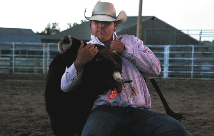 Justin Wade wrestles a steer for Chute Dogging competition at the EC Fairgrounds Tuesday June 16
