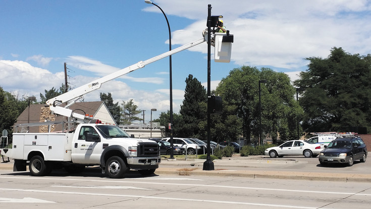 A worker removes a red-light camera on the corner of Littleton Boulevard and Broadway on Aug. 3. Photo by Jennifer Smith