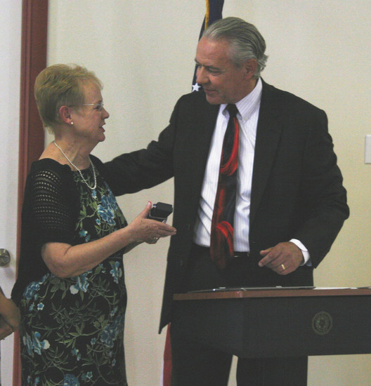 Congressman Ken Buck presents Sandy Swanson her father's Prisoner of War Medal seventy years after Petty Officer 2nd Class Merritt Eddy's release from a Japanese prison camp.