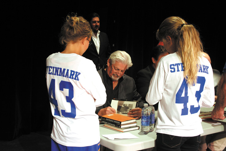 Wheat Ridge graduate, author and screenwriter Bower Yousse signs his book Freddie Steinmark: Faith, Family, Football, for Wheat Ridge students.