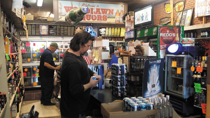 Bill Barnes, left, and Josh Engelhardt keep things moving at the busy Woodlawn Liquor store. The store's owner, Mark Mack, worries it won't be so busy if a proposal to allow liquor sales in all grocery stores passes. Photo by Jennifer Smith