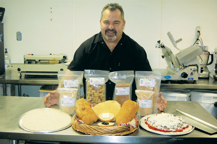 John Irvin, owner of Gluten Free Things in Arvada, stands with some of his gluten-free products, including pizza dough, pita bread, bread crumbs, English muffins and croutons. Courtesy photo