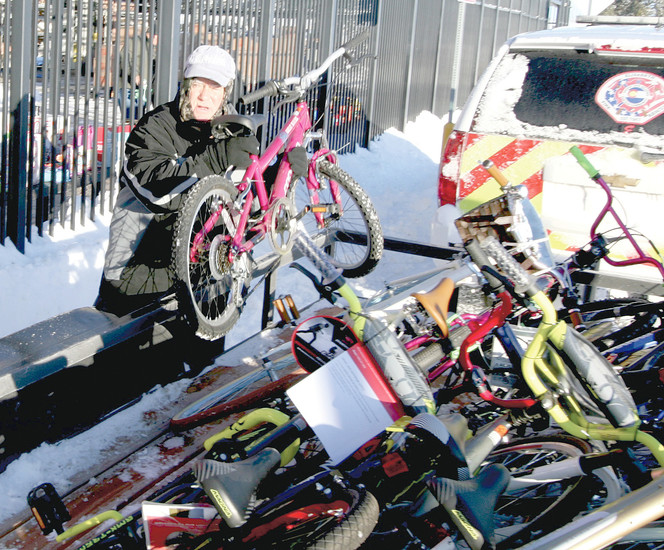 Retired firefighter John Ognie stacks bicycles.