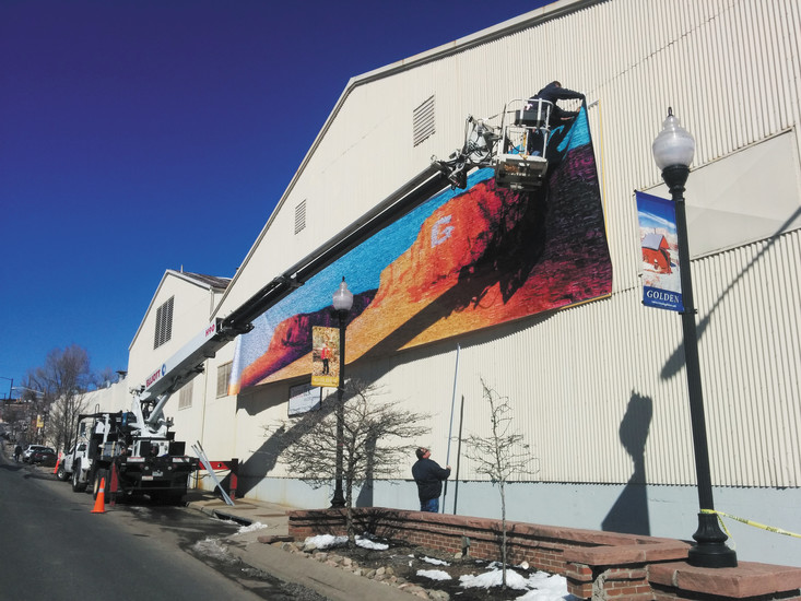 GURA's public art project is on display on the CoorsTek building at 9th and Washington Avenue. Crews worked to hang the large mosaic banner of community photos last summer. The template is based on a painting donated by local artist Jesse Crock of the North and South Table Mountains.