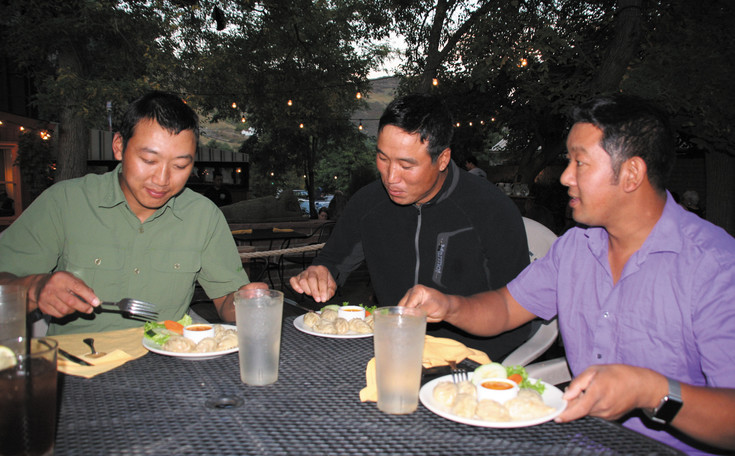 From left, Ngima Karma Sherpa, 33, and Danuru Sherpa, 36, enjoy a meal with Lhakpa Sherpa at his Sherpa House Restaurant and Culture Center in Golden. Ngima and Danuru, both from the Khumbu region of Nepal near the Himalayas, are professional mountaineering guides and lead tourists to summit Mount Everest—the highest mountain in the world.