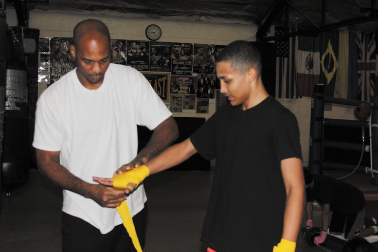 DaVarryl Williamson, a former heavyweight boxing champion, wraps the hand of Englewood Middle School student Cayden Hubbard before Hubbard begins the workout.