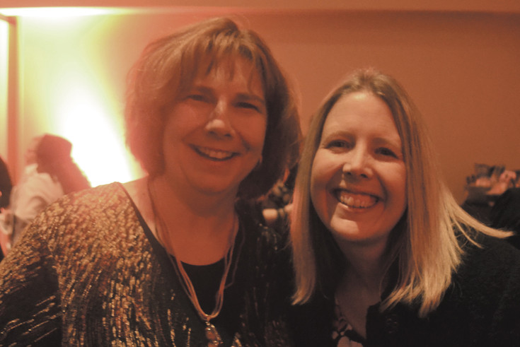 Dana Rinderknecht, of the Community First Foundation, and Alison Trembly, of the Arvada Economic Development Association, pause in their silent auction hunt for a photo.