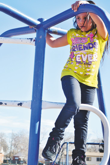 Janelle Gillotte takes a moment to climb to the top of this metal play structure. The structure is one of several that's been on the Lawarence Elementary playground for more than 20 years.