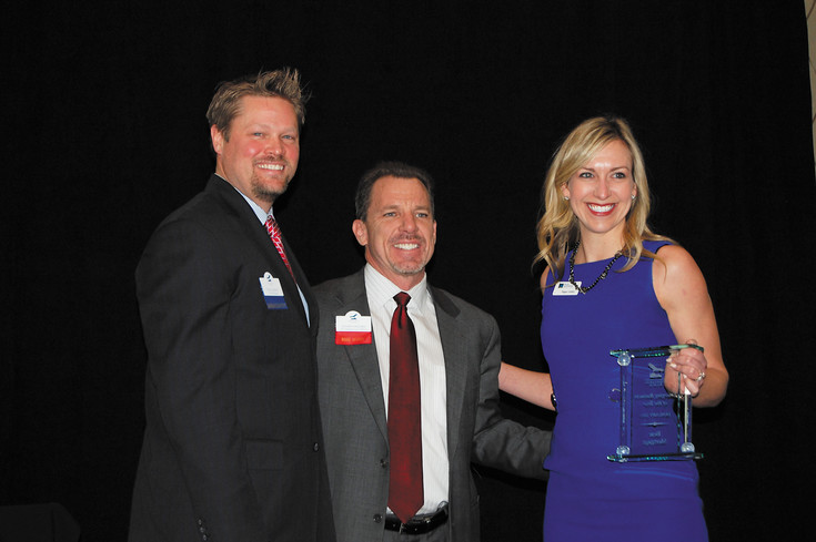 Justin Vaughn, center, poses with Tim and Megan Lindsey after they accepted the award for Emerging Business of the Year. Their company, Bear Mortgage Inc., tied with Seven Stones for the award.