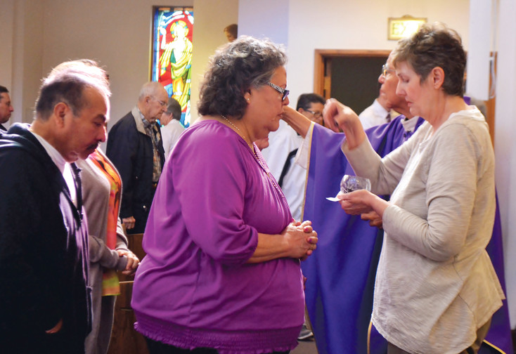 Blanca Alvarado, a parishioner of Arvada's Shrine of St. Anne's Catholic Church, receives ashes during the church's Ash Wednesday and Lenten celebration.