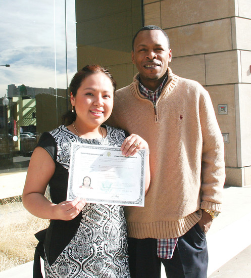 Susam Encalade holds up her certificate of citizenship outside of the History Colorado Center in downtown Denver after a naturalization ceremony Feb. 17. Accompanying Encalade at the ceremony was her husband, Donnell, pictured, and her brother.