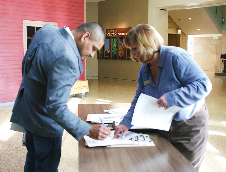 Lisa Doran with the Colorado secretary of state�s office assists Jose Ceballos, left, with the voter registration form after a special President�s Day naturalization ceremony Feb. 17 at the History Colorado Center in downtown Denver.