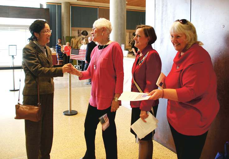 Wendy Zhou, left, receives her American flag and program from, from left, Karen Bartos, Marcy Kimminau and Jill Freeman who are members of the Golden-based Mount Lookout Chapter of the National Society Daughters of the American Revolution, Feb. 17, at the History Colorado Center in downtown Denver.