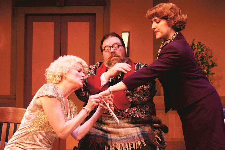 "Glamorous/devious Lorraine Sheldon (Martha Harmon Pardee) looks at Maggie Cutler's (Taylor Nicole Young) gift as the horrible houseguest, Sheridan Whiteside (Eric Fry), looks on in a scene from ""The Man Who Came to Dinner"" at Town Hall Arts Center."