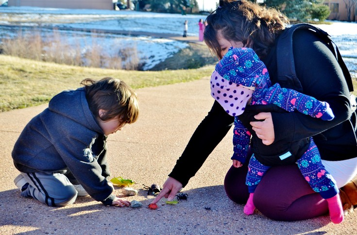 With the help of his mom, Brooke, Liam Royer carefully aligns his bugs, rocks and beans in a nature pattern as his sister watches.