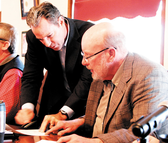 Larry Ross, chairman of the board of county commissioners, signs loan paperwork under the guidance of County Attorney Wade Gateley.
