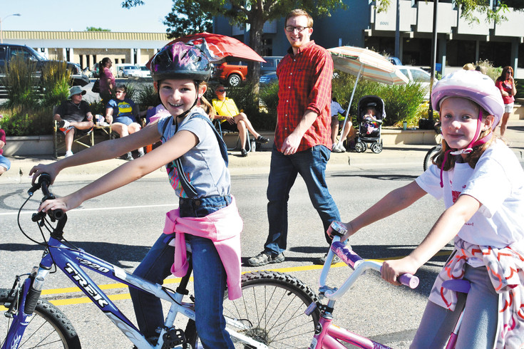 Foster Elementary students Lucy George, left, and Darby McMahon, right, roll along on their bikes during the 2015 Arvada Harvest Festival.