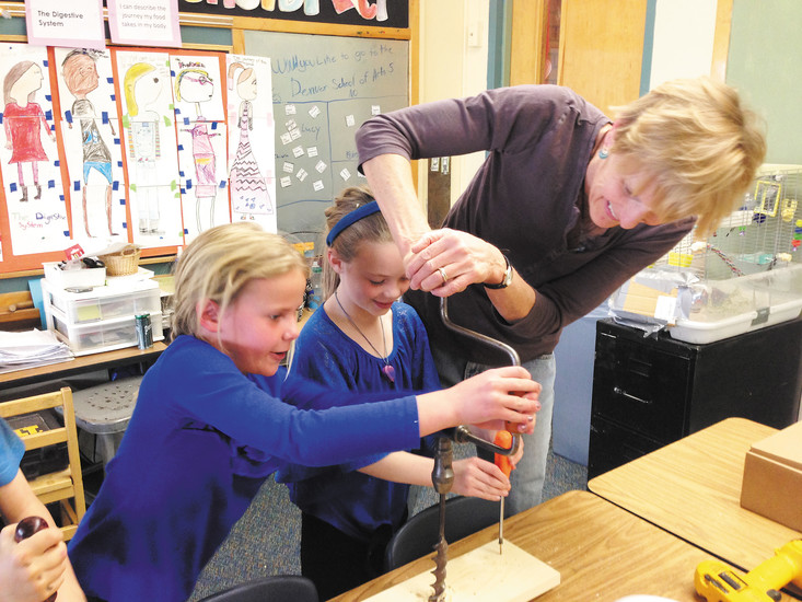 From left, Chiara Wilczewski and Evie Garrington work with teacher Judy Racine to learn how to use different types of screwdrivers needed for building wooden pinball machines for their simple machines learning unit.