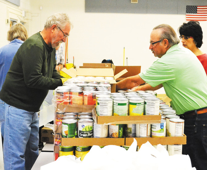 Jim Scharfenberg, left, converses with other Arvada Community Food Bank Backpack-A-Roo volunteers to figure out the packing order for the food.