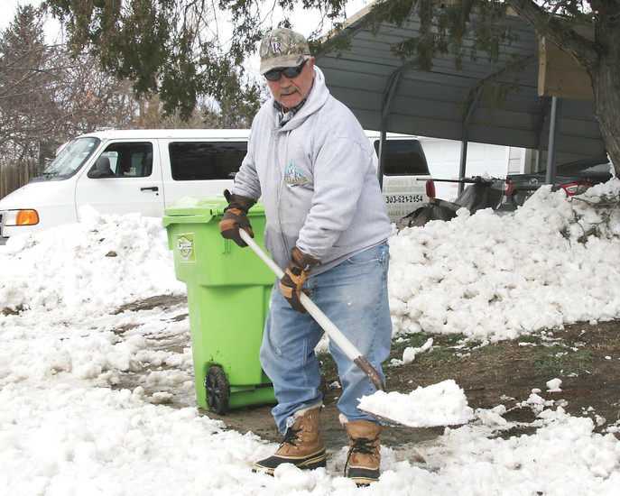 John Pimental, of Kiowa, piles snow from the edge of his lawn to a nearby tree as part of his winter watering plan.