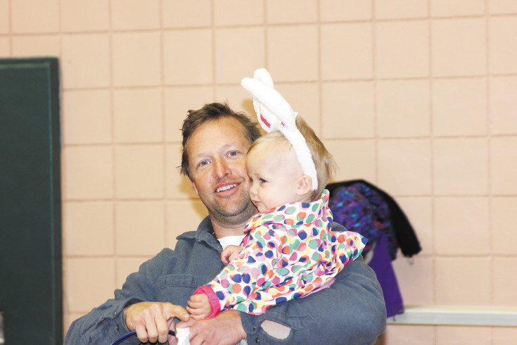Cody Reece holds his year-old daugther Lila as they wait for the start of the March 25 Englewood Great Egg Scramble. Reece said his daughter liked her bunny ears and was looking forward to the event originally scheduled to be held at Miller Field. But, because of the snow, it was moved to the gymnasium at the Englewood Recreation Center.