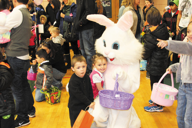 Elena Galondo, 3, gets a hug from the big white bunny while her cousin Abraham Martine, 4, waits his turn during the March 25 Englewood Great Egg Scramble. The heavy snow forced organizers to move the event inside. It was held in the gymnasium of the Englewood Recreation Center and about 200 children took part in the event.