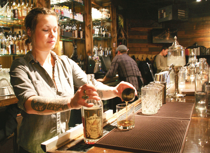 Carly Raemer, assistant manager and bartender at the Golden Moon Speakeasy, located on Miner's Alley in Golden, pours a glass of the Golden Moon Colorado Single Malt Whiskey.