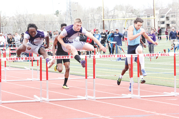 Mat Hanson, left, and Lutheran teammate Kharon Hall are almost tied as they head for the finish line of the 110-meter high hurdles at the April 22-23 Liberty Bell Invitational Track Meet. Hanson finished first and Hall finished second as the Lions finished second in the team standings.