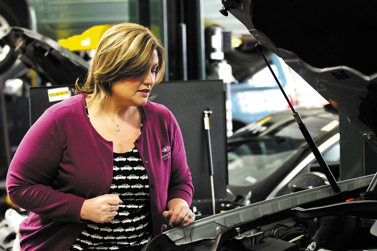 "Sarah Vowell peeks under the hood of a car in the garage at the Christian Brothers Automotive store in Parker on Friday, April 8. Vowell focuses on the ""business side"" of the operation while her husband Adam manages the garage."