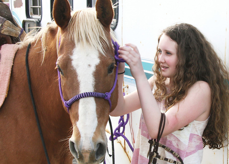 Kaelie Denton of Elizabeth tacks up Tuffy before drill practice on May 6. Denton is in her first year on the Blazing Saddles Drill Team and enjoys riding in parades.