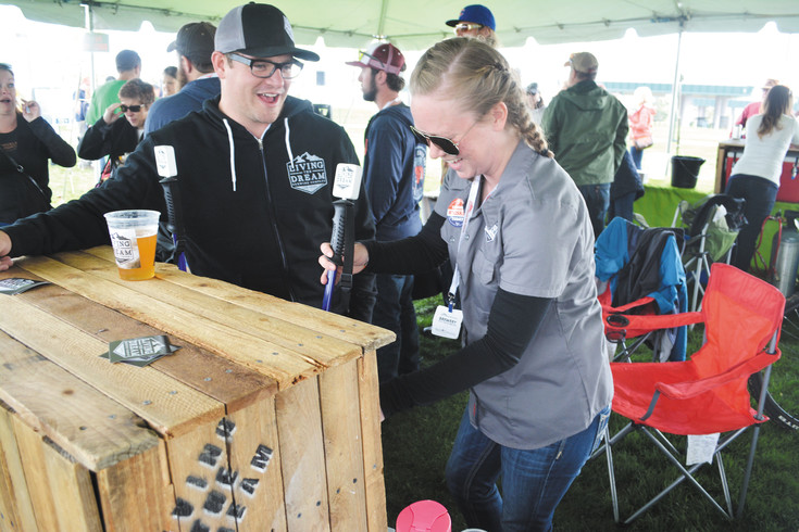 Abby Cadogan of Living the Dream Brewing Company pours a sample of the brewery's Empty Trophy Case IPA at the South Denver Beer Festival on May 8.