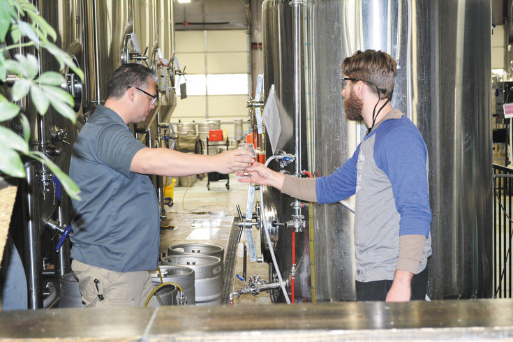 Living the Dream Brewing co-owner and brewmaster Jason Bell, left, and assistant brewer Jerod Scott, taste a beer fresh out of the tank on April 29. Bell and Carrie Knose opened the brewery on Dumont Way in 2014.