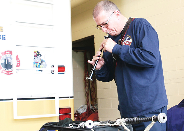 Mike West seasons the read on his chanter ahead of practice. The band practices weekly at South Metro station 34.