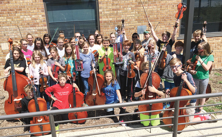 Some of the Bell Middle School orchestra students hold up their instruments and trophies for a celebratory picture. The orchestra competed in the Music in the Parks competition May 13 at Ralston Valley High School in Arvada, and won first place for middle school out of five schools from across the state in their category. Plus, the orchestra got a trophy for getting 98.3 points out of 100, earning them a superior ranking. Courtesy photo