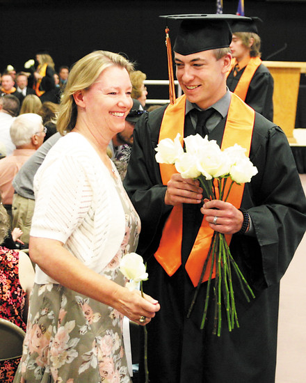 Senior Coleton Wenz presents a Rose to his mother Larra. Each year, graduation seniors at Kiowa High School present flowers to family members and friends in the audience.