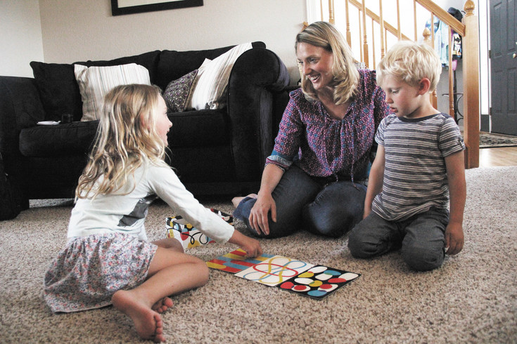 Jasmyne Kettwick plays a board game with her daughter, Kingsley, 5, left, and her son, Cannon, 2. Kettwick, a family therapist, says it is crucial for working parents to find a daily routine in order to spend quality time with their children.