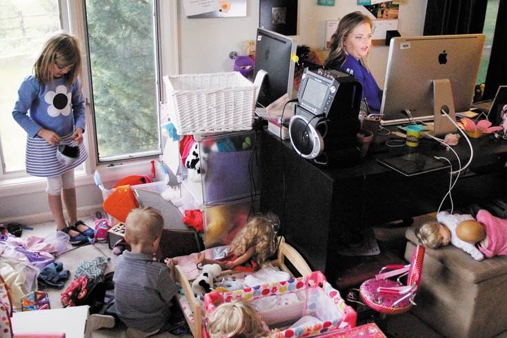 Alaina Jones, 6, left, and her brother Jack, 2, center, play as their mother Erin sits at her desk in her home office in Parker. Jones says her ability to work during the day depends on whether or not Jack takes a nap.