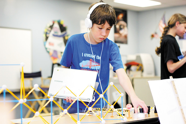 "Nikolas Tucker (11) makes final adjustments to the game ""Drifting Driftway"" that he and his partners created for the Pine Lane Elementary Planet Protectors Carnival on May 31. Fourty-two students designed games, did research and promoted awareness of global issues for the event."