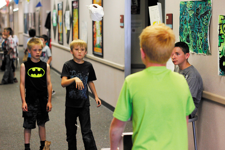 "Michael McHenry (7), left, watches as Riley Lafollette (8), center left, tosses a roll of toilet paper into a box held by Dylan Waite (12), center right, as Brennan Koontz (12), right, looks on. Waite and Koontz created the game ""Toilet Funtime"" for the Planet Protectors Carnival at Pine Lane Elementary on May 31. The event raised $1,100 for various nonprofit groups."