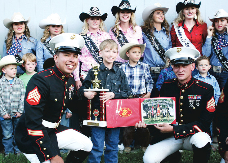Seven-year-old, mutton buster Jack Daily poses with his trophy and members of the Marine Corps Mounted Color Guard at the Elizabeth Stampede and Rodeo on June 4. Boys and girls ages 4 through 7 are eligible to ride sheep between events at many rodeos, and mutton bustin' has become a big part of rodeo culture.