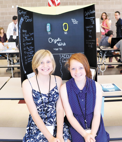 From left - Emily Harris and Cassandra Smyth, sixth graders at Pine Lane Elementary, present their Ongaku Watch, a collaboration of a Fitbit and Apple Watch, at the June 6 Student Expo. Ongaku means means music in Japanese and stems from the girls' musical talents - Smyth plays the piano and Harris plays the guitar.