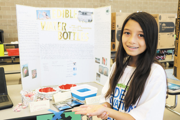Rachel Bloomfield, a fourth grader at Pine Lane Elementary School, demonstrates her edible water bottle project. The 10-year-old researched how chefs make food look like caviar eggs and used similar materials to create a gooey, clear water bottle.